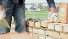 stock-footage-construction-mason-worker-bricklayer-installing-red-brick-with-trowel-putty-knife-outdoors